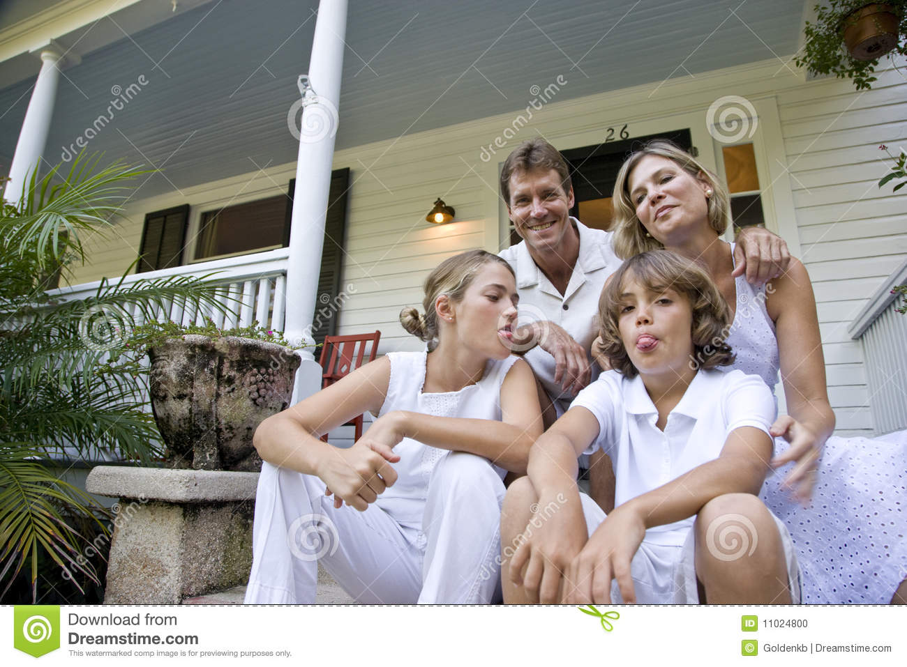 Family Sitting Together On Front Porch Steps Stock Photo