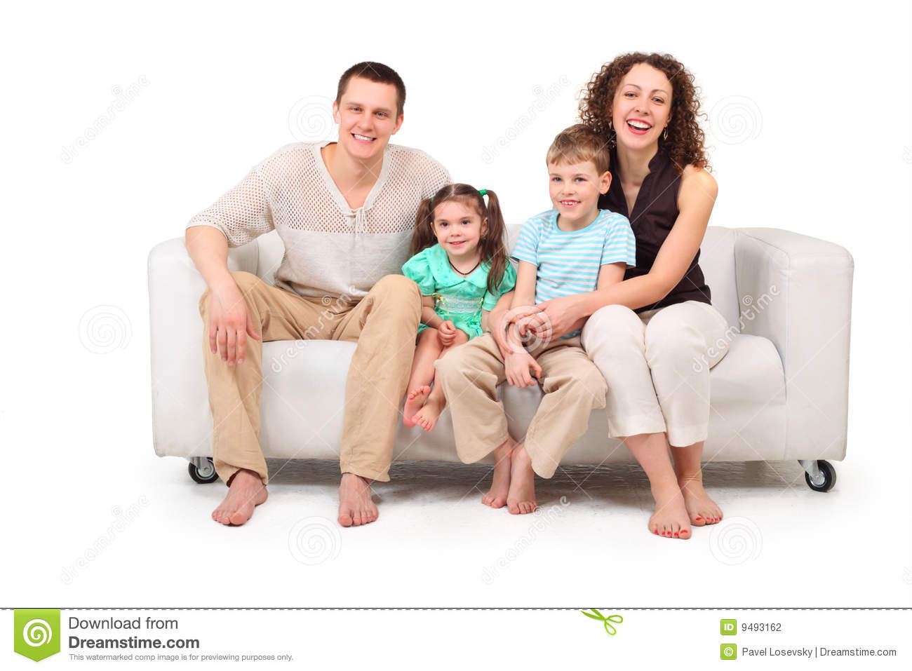 Family with two children sitting on white leather sofa on white.