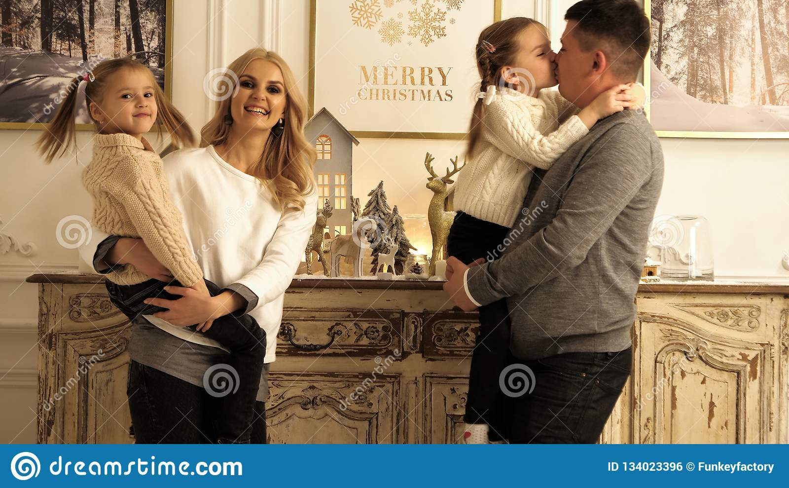 Family smiling to the camera in living room on christmas evening.
