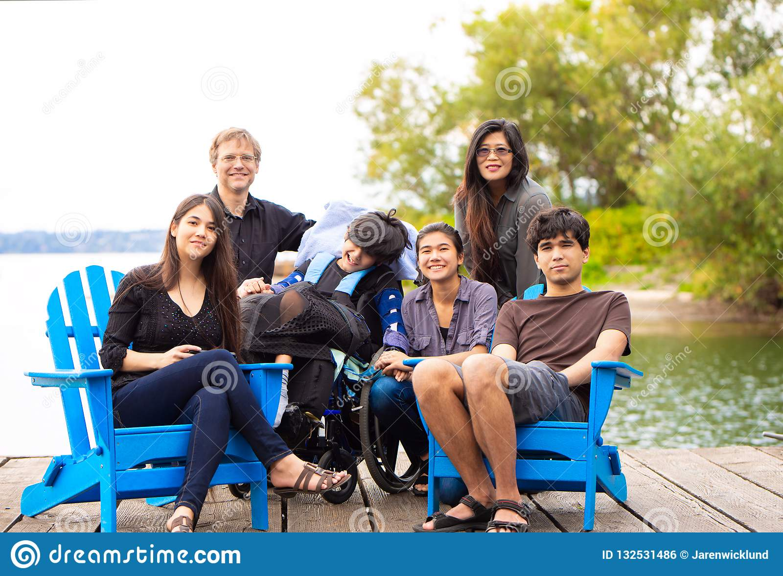 Family with special needs child sitting outdoors together in sum