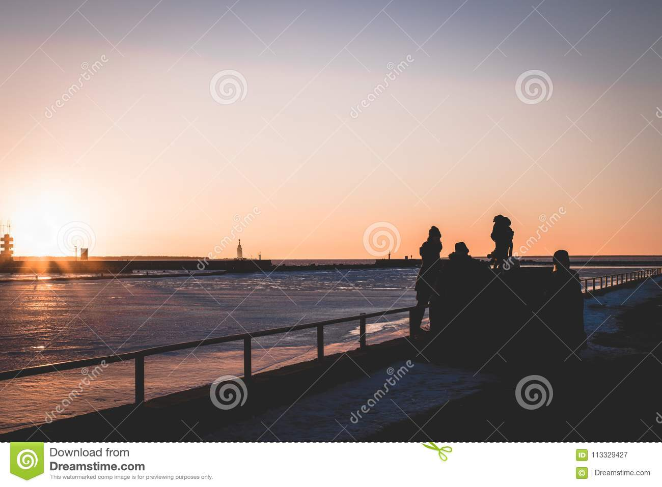Family spending time during the sunset by the sea