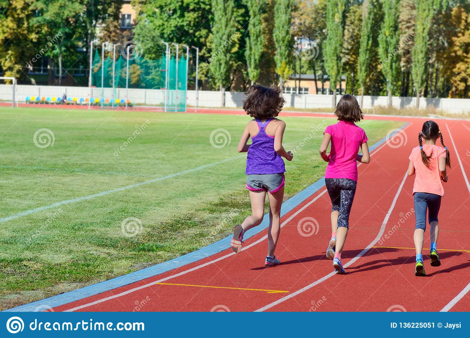 Family sport and fitness, happy mother and kids running on stadium track outdoors, children healthy active lifestyle
