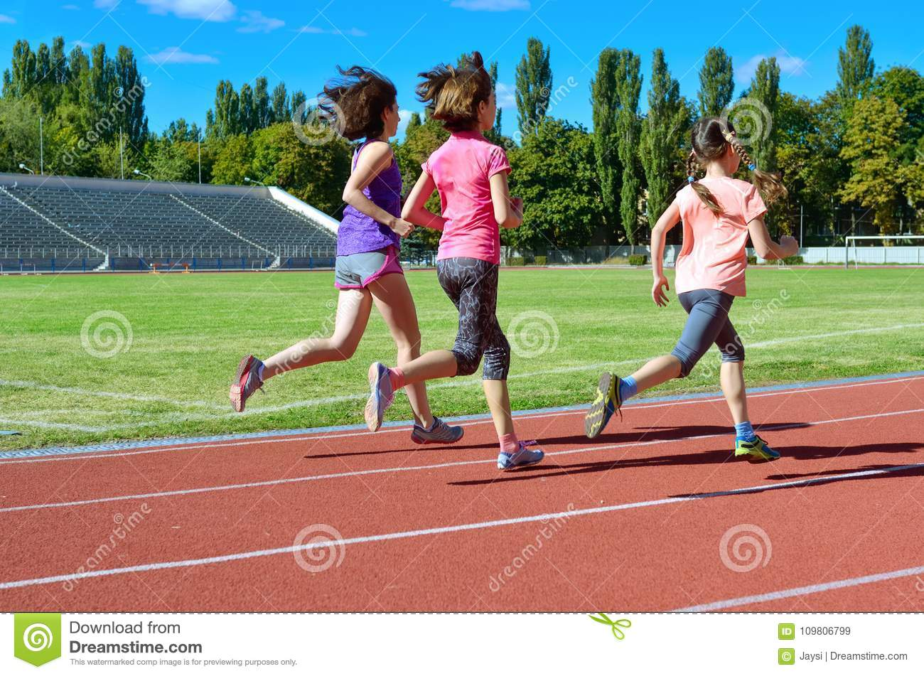 Family sport and fitness, happy mother and kids running on stadium track outdoors, children healthy lifestyle concept