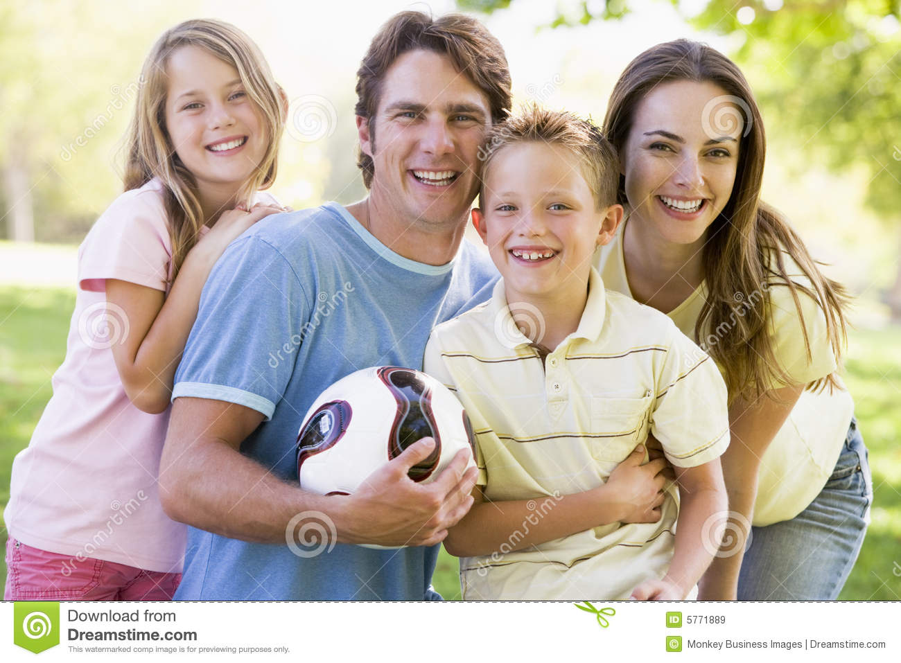 Family standing holding volleyball smiling