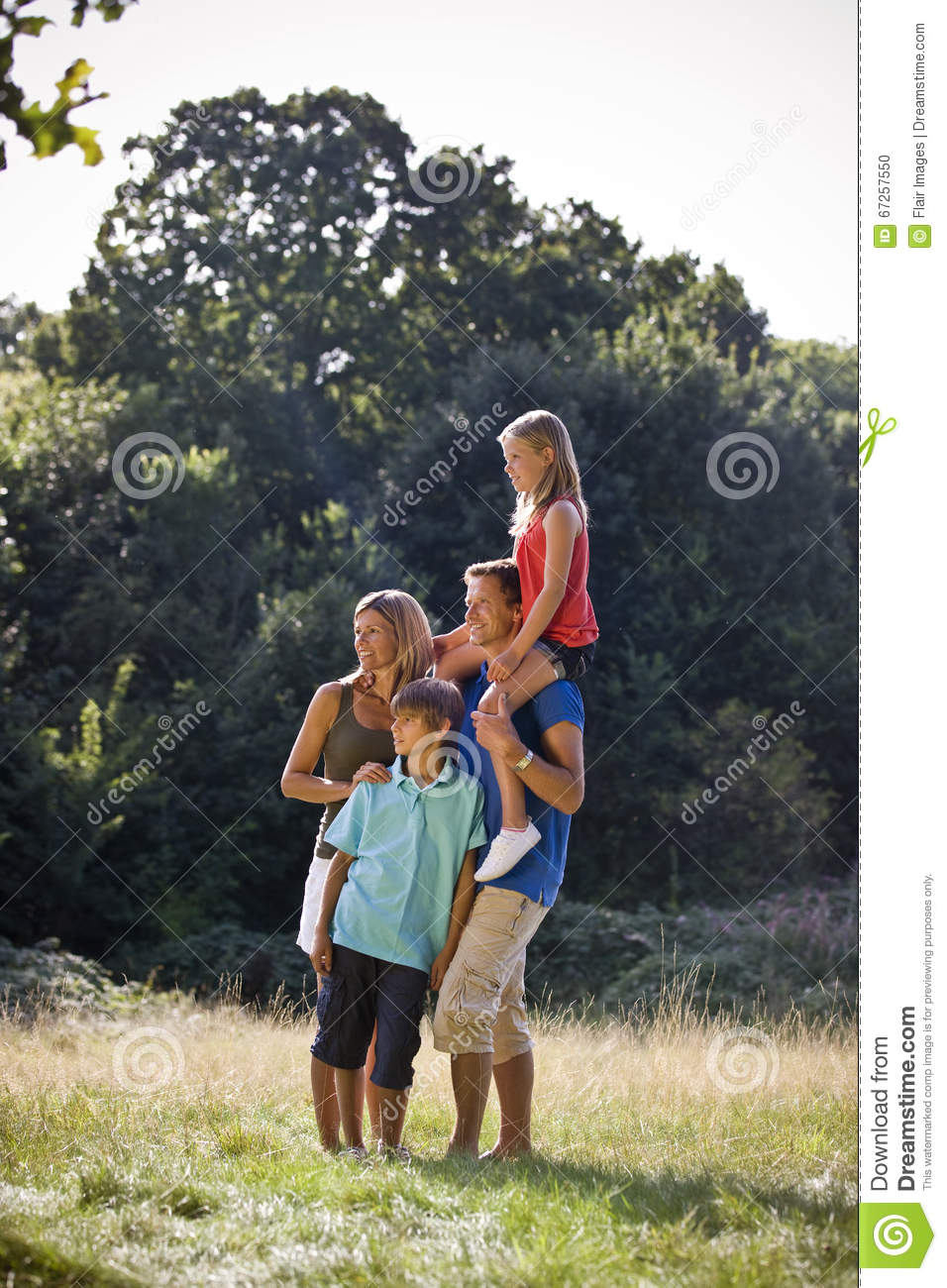 A family standing in a park, father carrying his daughter on his shoulders