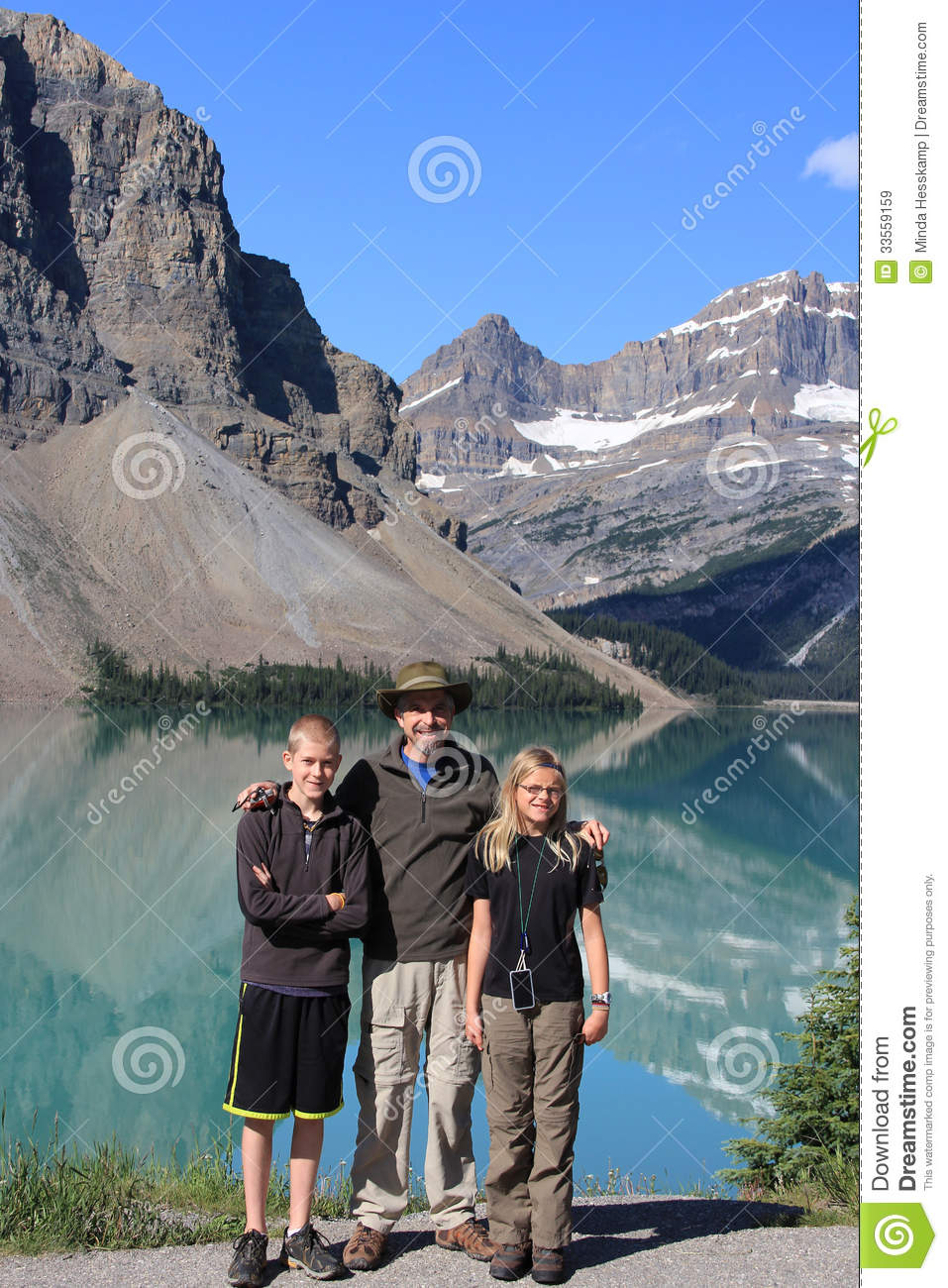 Family Stands In Front Of Bow Lake With Mountain
