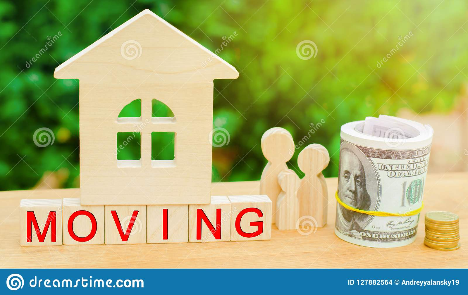 Family stands near the miniature house with money and the inscription `moving`. real estate concept. moving to another apartment,