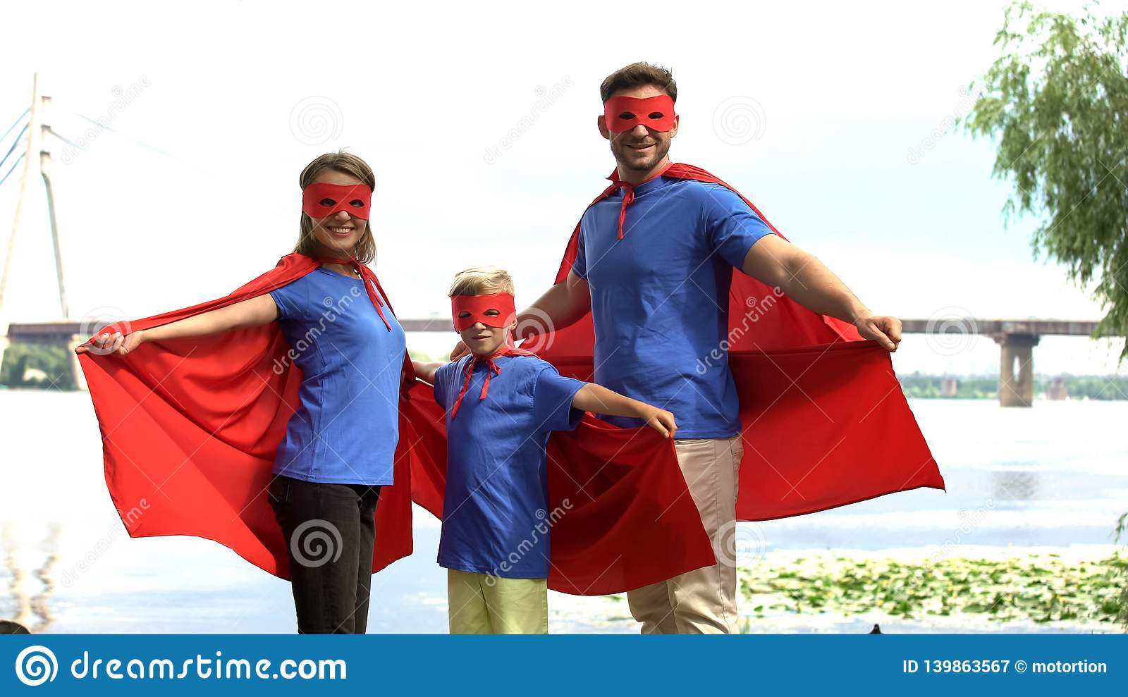 Family in superhero costumes posing for camera, togetherness and outdoor rest
