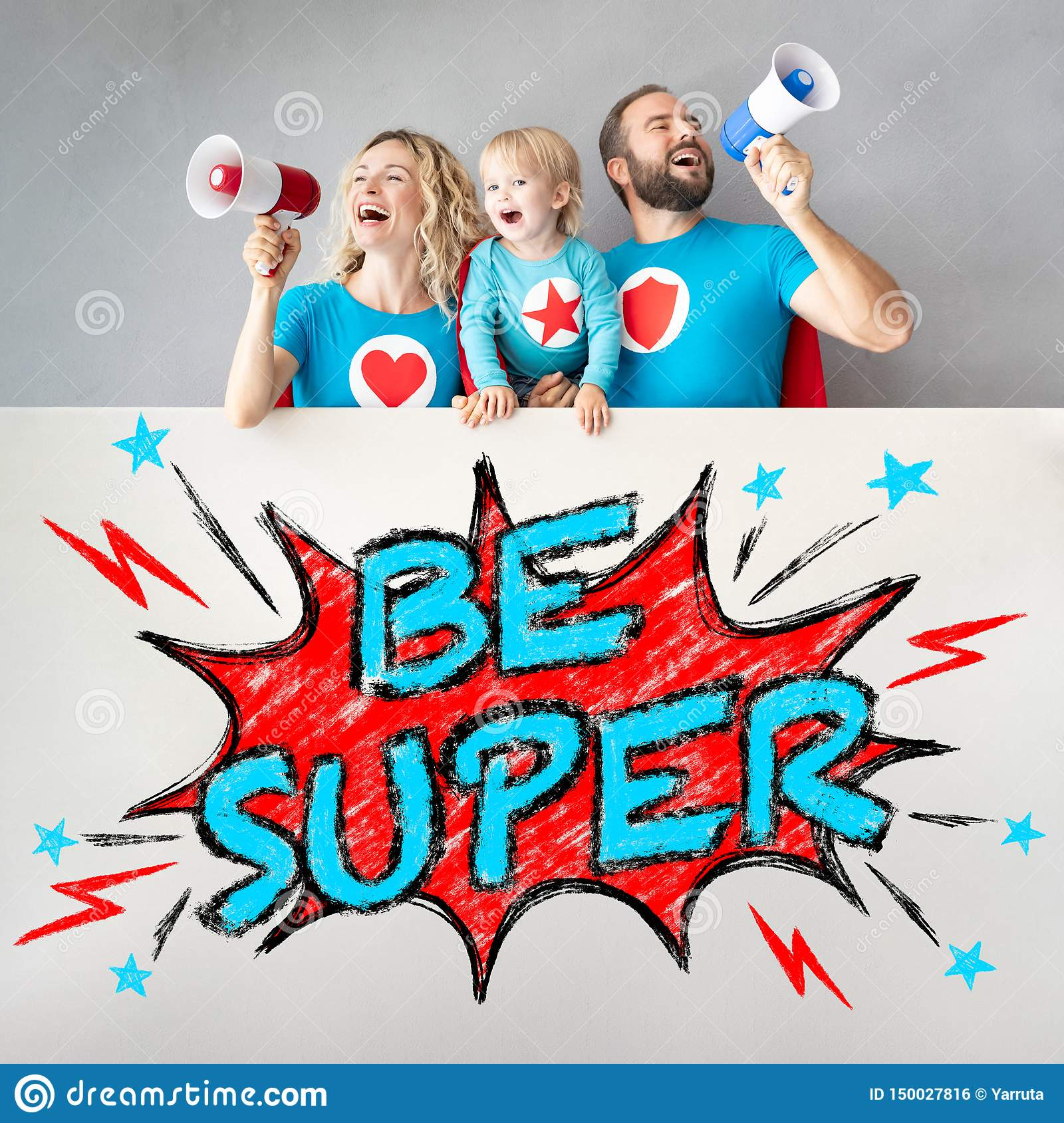 Family of superheroes holding banner