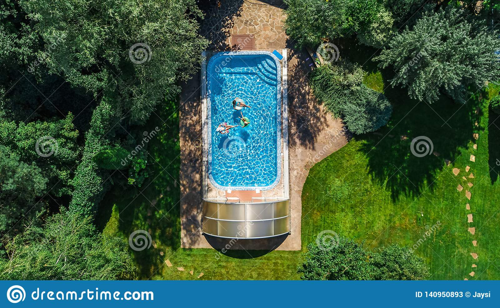 Family in swimming pool aerial drone view from above, happy mother and kids swim on inflatable ring donuts and have fun in water