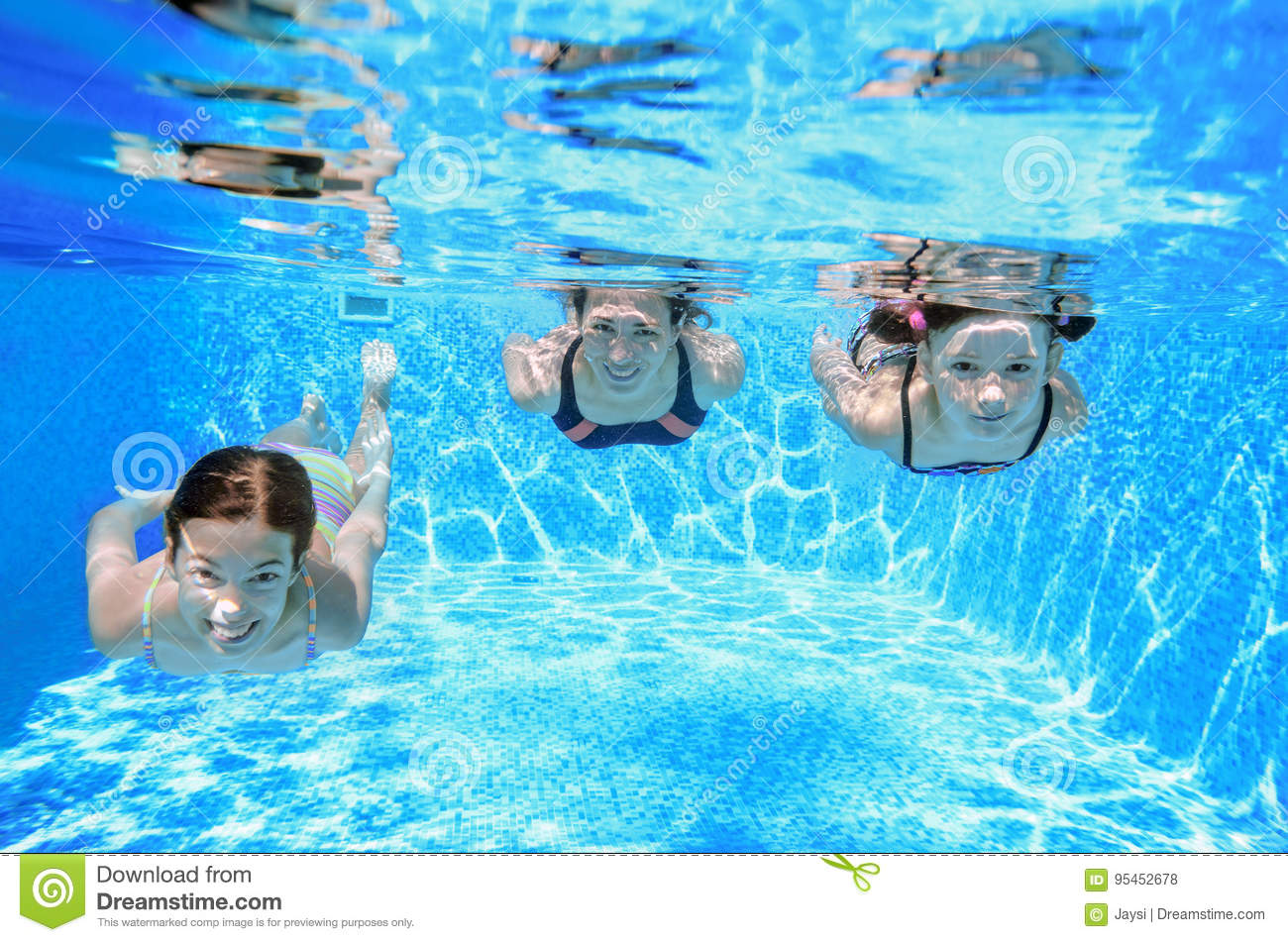 Family swimming in pool under water, happy active mother and children have fun, fitness and sport with kids