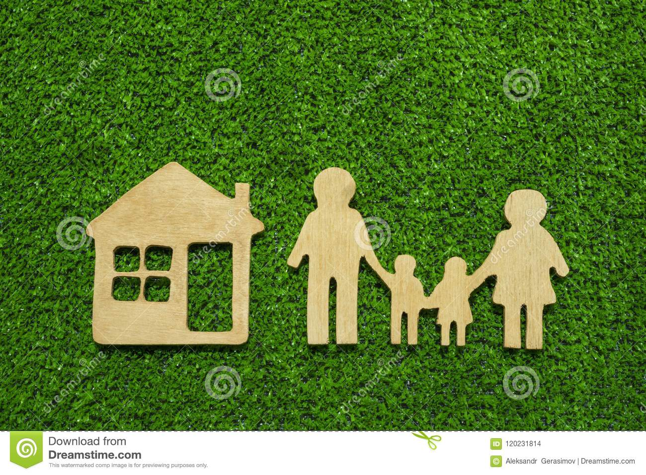 Family symbols and houses made of natural wood on the background of green grass symbolize the eco-house