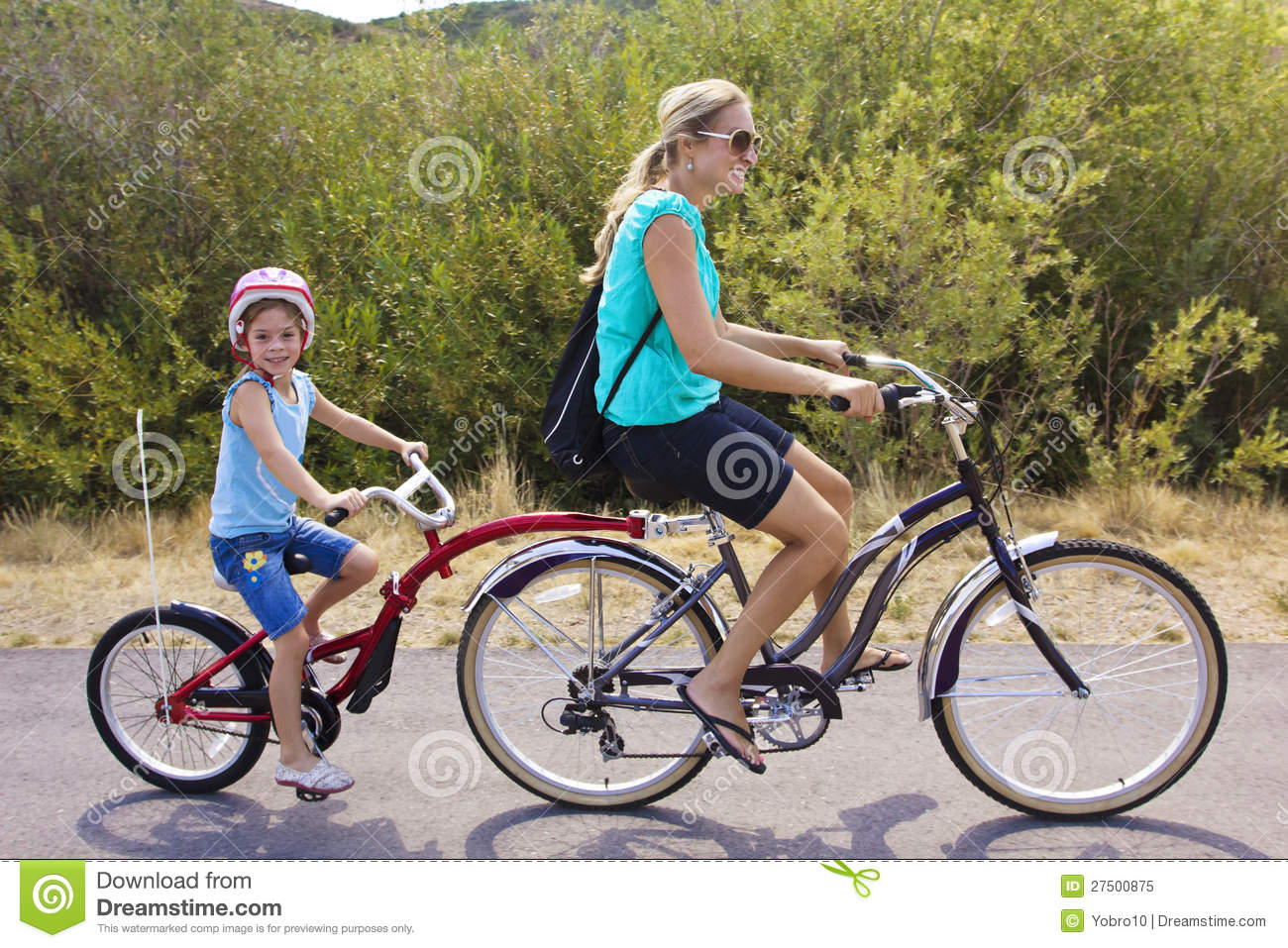 ... and daughter enjoying a tandem bicycle ride together on a bike path