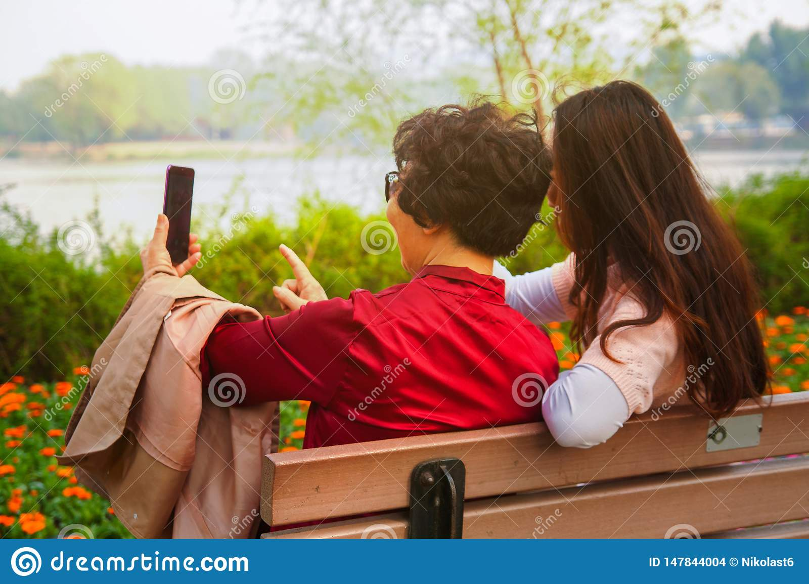 Family, technology and people concept - happy daughter and senior mother with smartphone sitting on park bench and taking