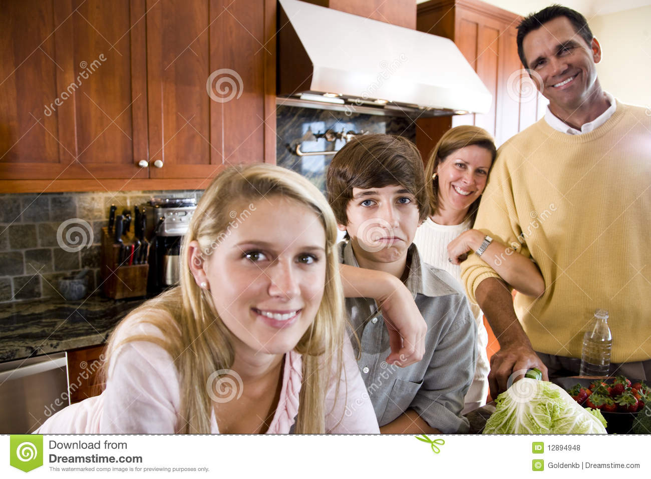 Family with teenager kids in kitchen, boy frowning