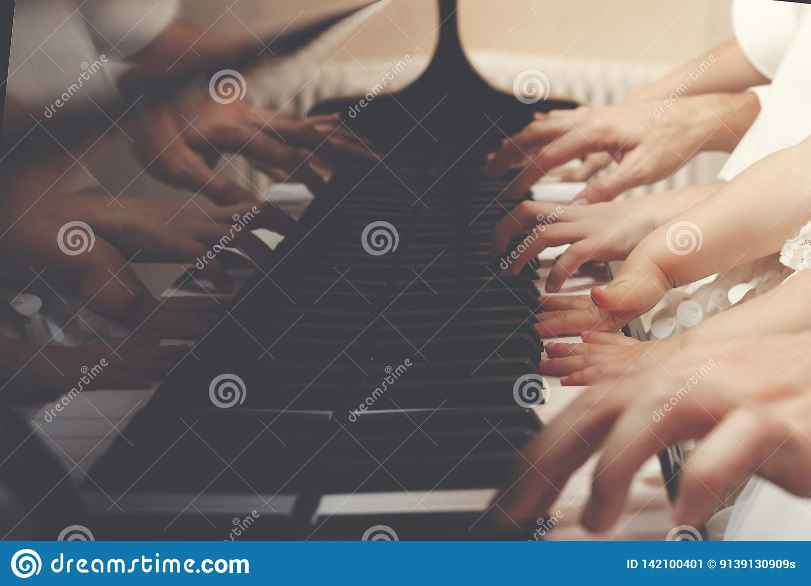 Family of three members playing a piano together