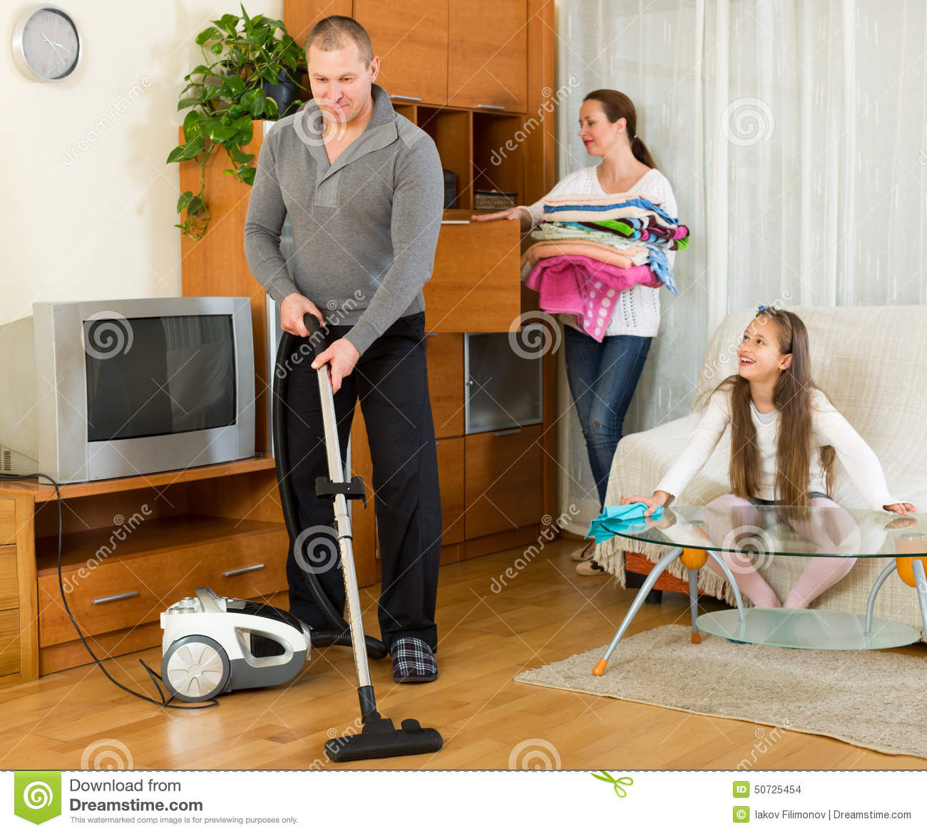 Family Of Three Tidying Up A Room Stock Photo Image