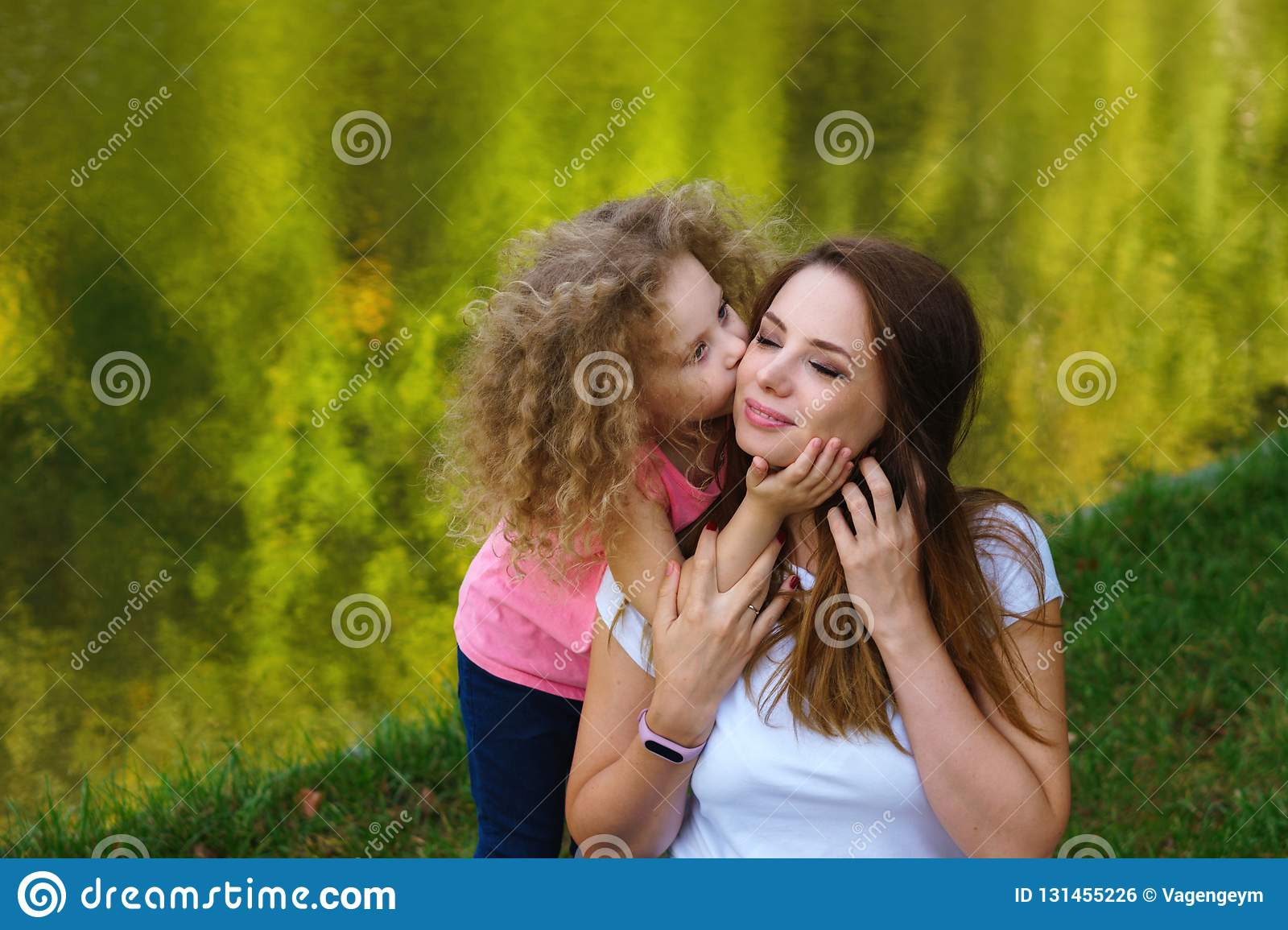 Family time. Mother and daughter on river bank. Little girl hugs and kisses mother