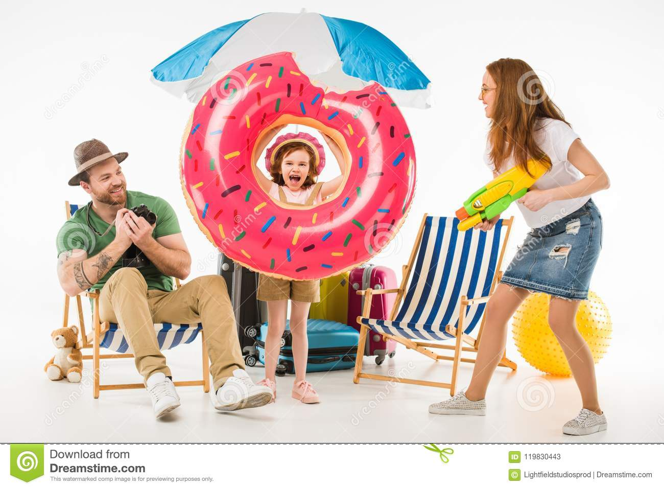 Family of tourists with flotation ring, camera and water gun