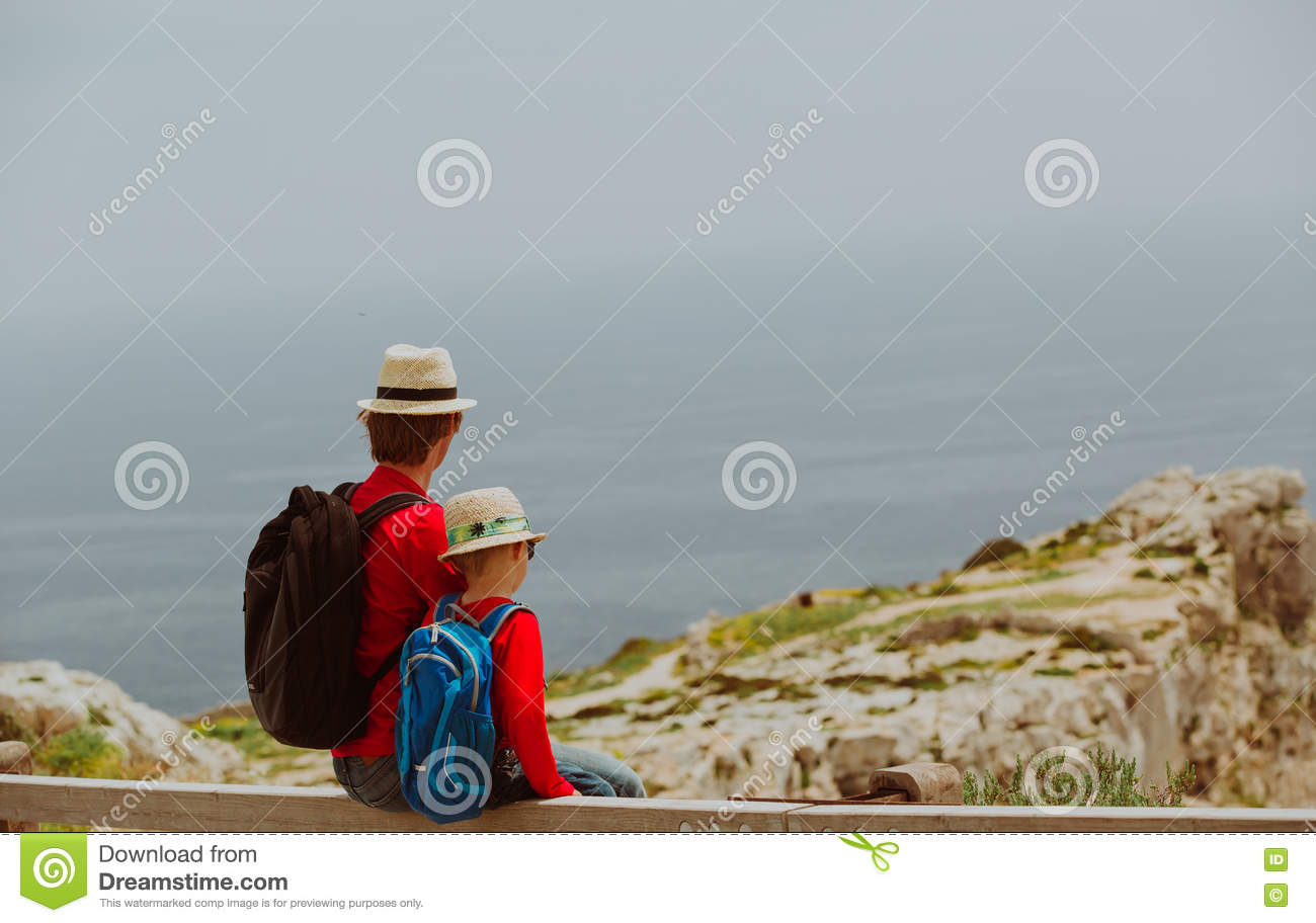 Family travel -father and son hiking with backpack in mountains