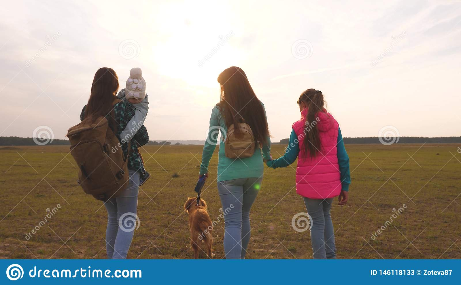 Family travels with the dog on the plain. teamwork of a close-knit family. mother, little child and daughters and pets