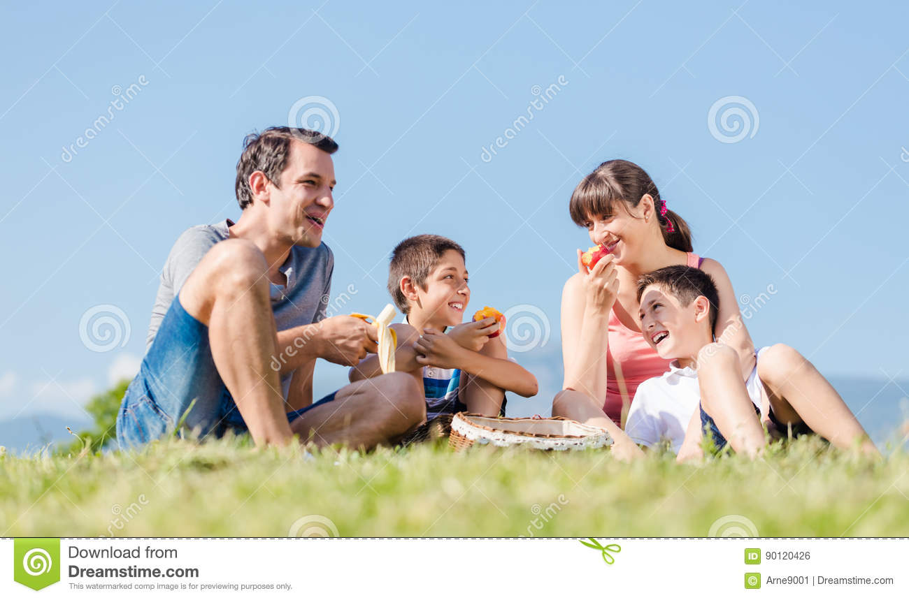 Family with two sons having a picnic with fruits in park in summer