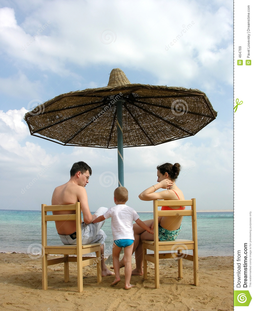 Family under umbrella on beach