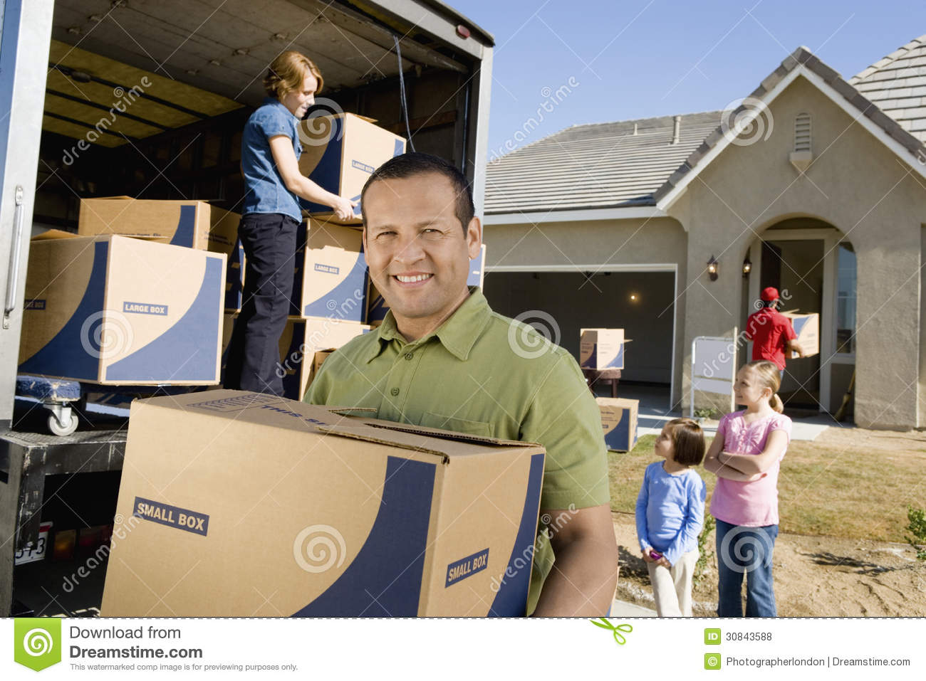 Family Unloading Delivery Van By New House