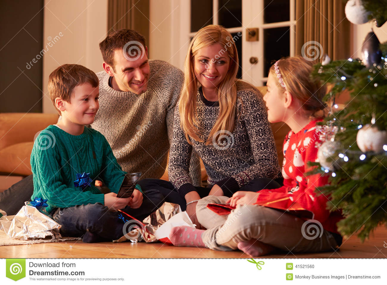Family unwrapping gifts by christmas tree stock photo