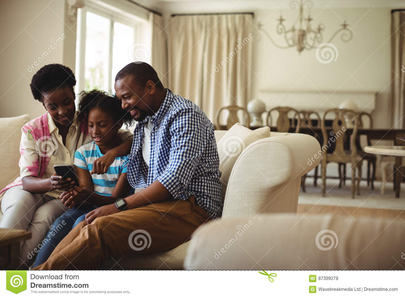 Family Using Mobile Phone In Living Room Stock Photo