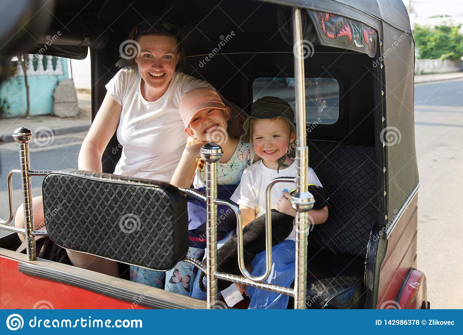 Family on vacation, mother and kids sitting in tuk-tuk, having fun