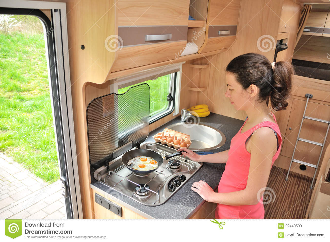Family vacation, RV holiday trip, travel and camping, woman cooking in camper, motorhome interior