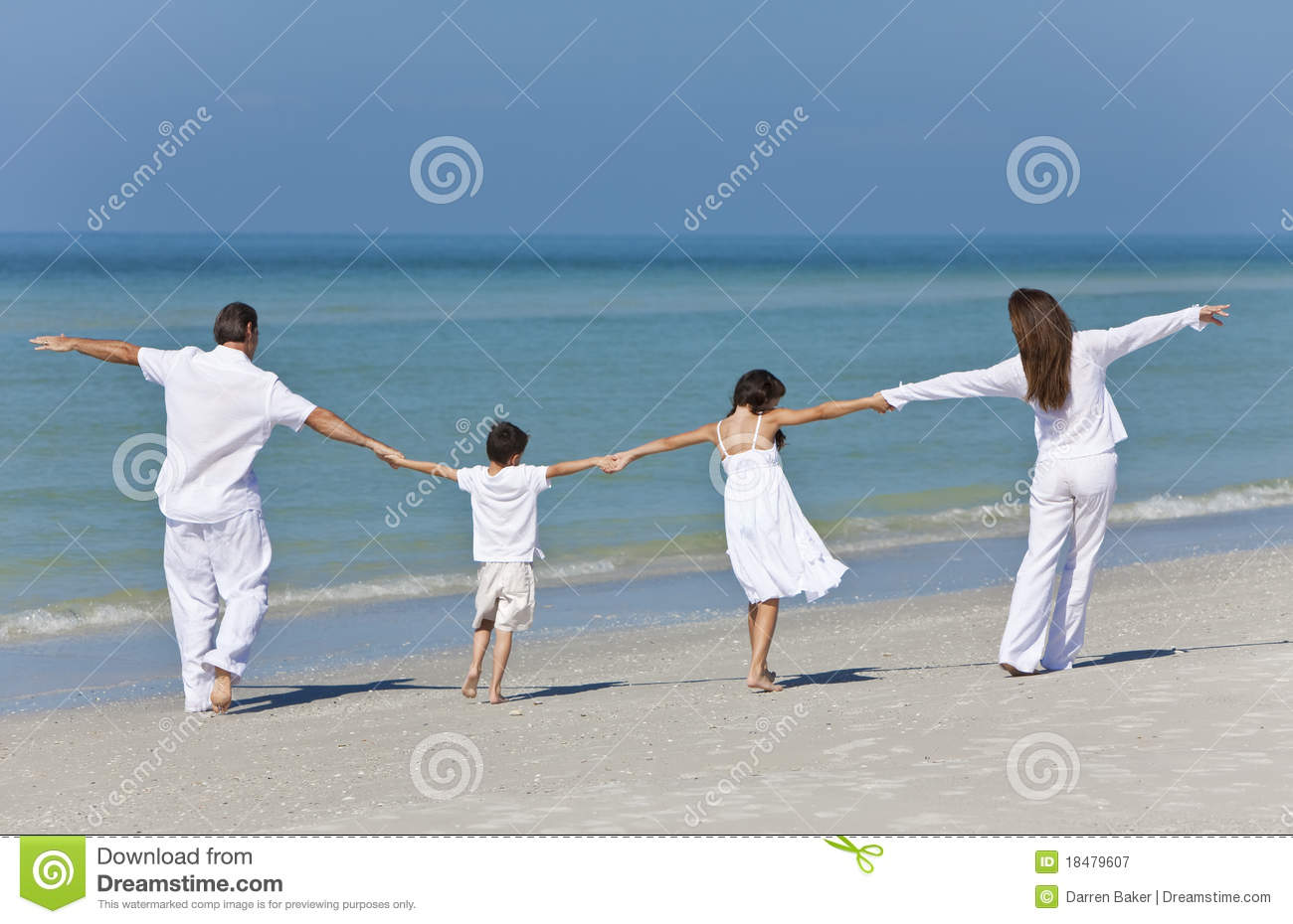 Family Walking & Holding Hands On Beach