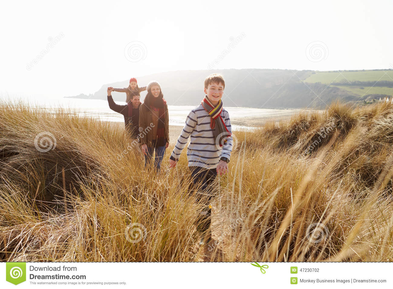 Family Walking Through Sand Dunes On Winter Beach
