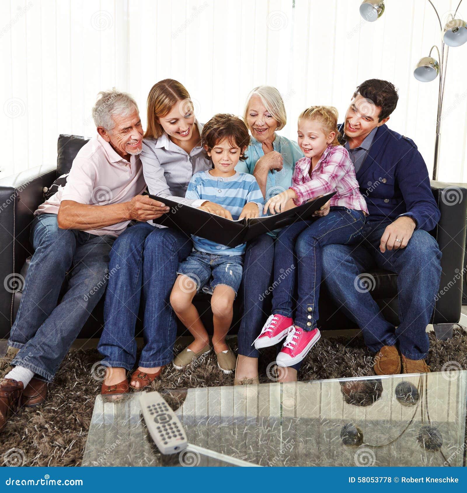family watching photo album in living room stock photo