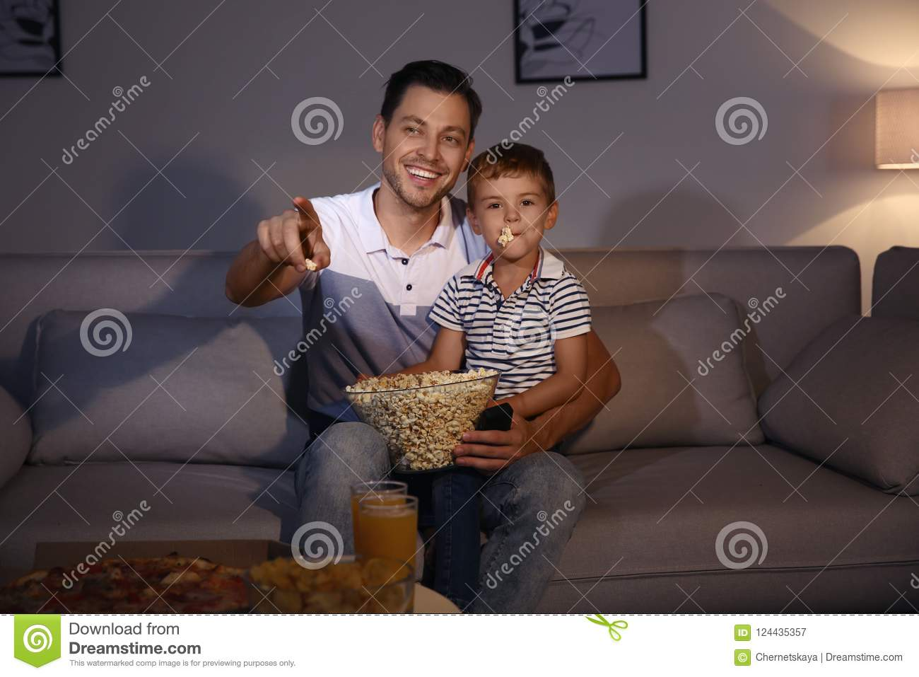 Family watching TV with popcorn in room at time