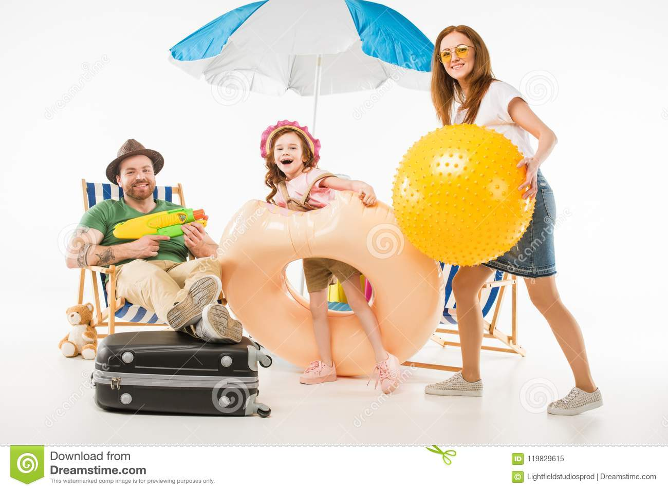 Family with water gun, flotation ring and ball