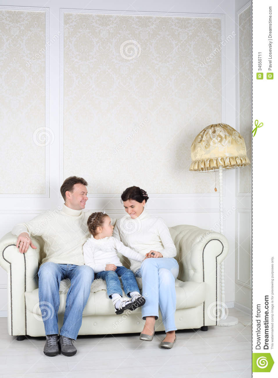 Family In White Sweaters And Jeans Sit On White Sofa Stock Image Image 34550711