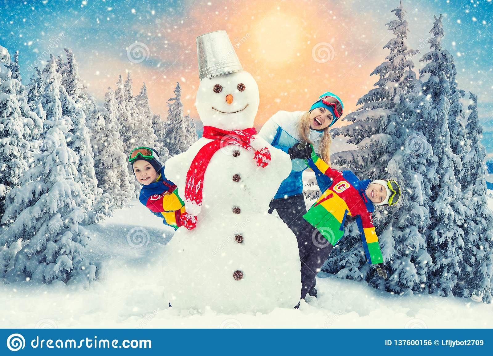 A family in a winter snowy forest mold a big snowman.Family winter fun for Christmas vacation.