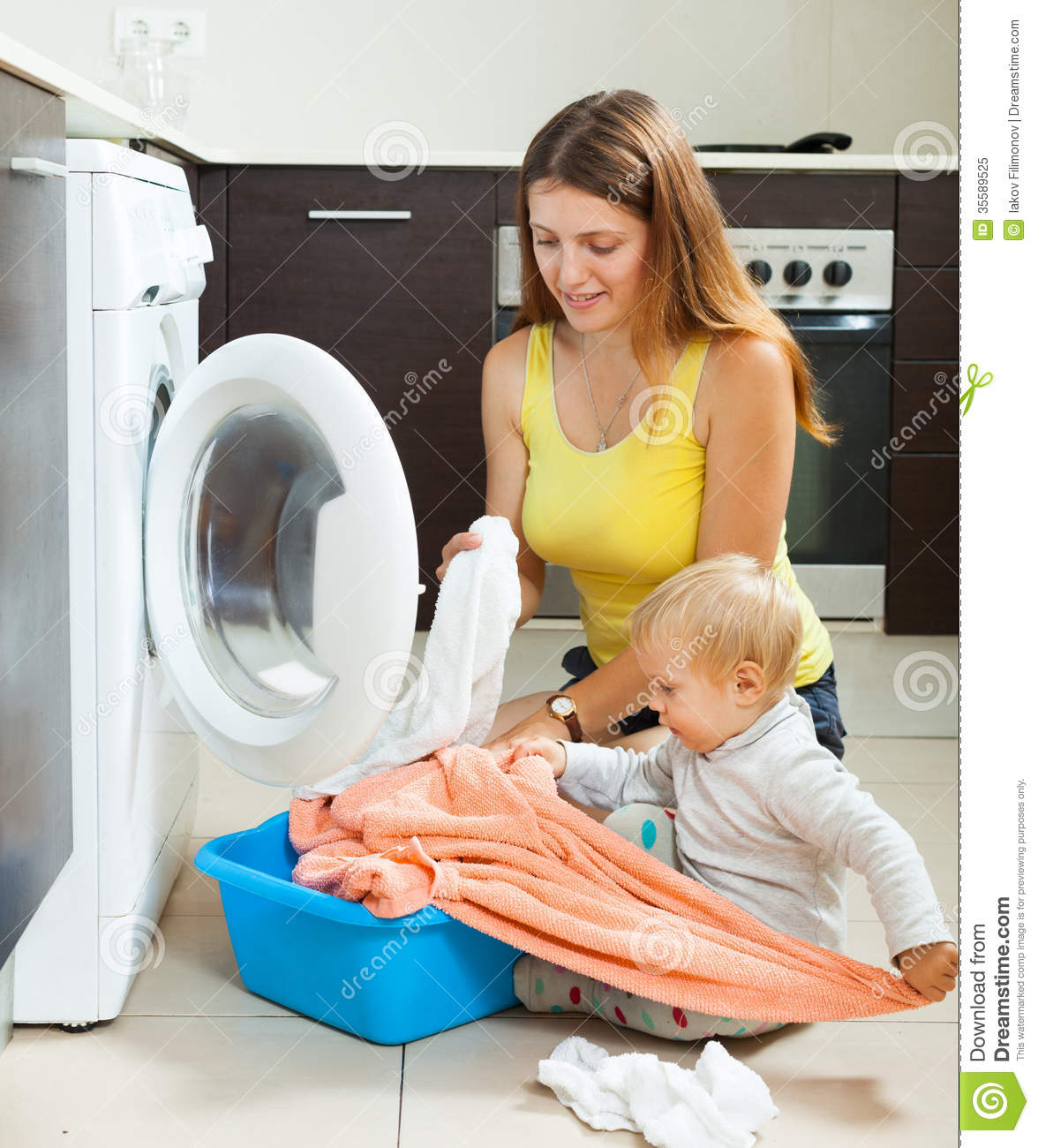 Family Woman Putting Clothes In To Washing Machine Royalty