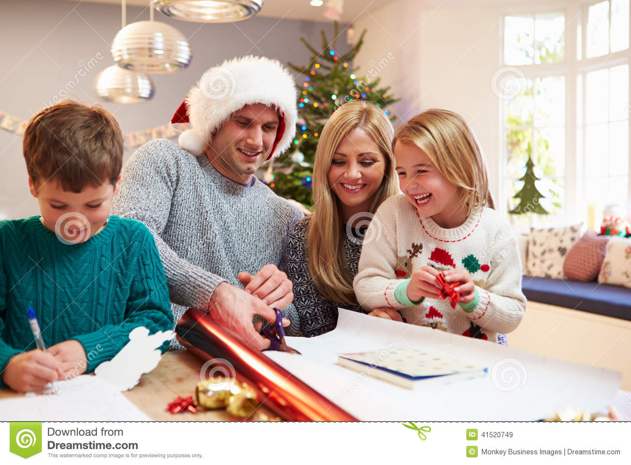 Family Wrapping Christmas Gifts At Home Stock Photo