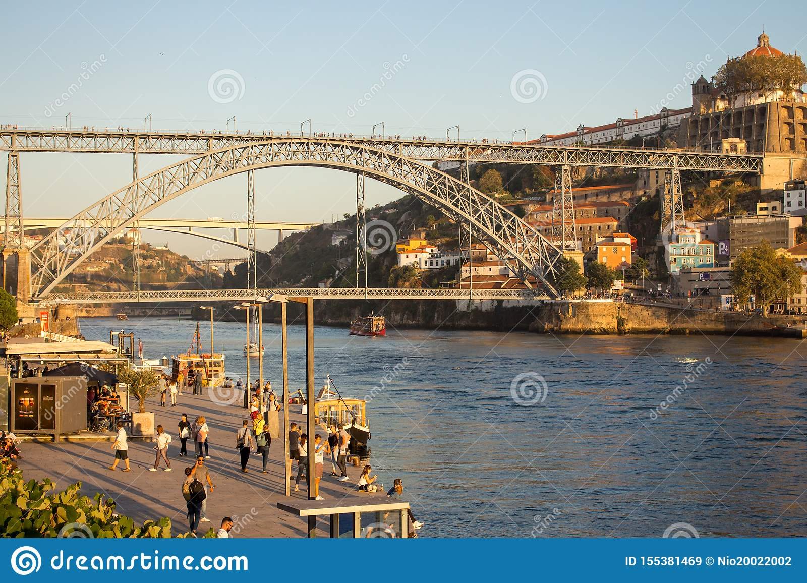 Famous bridge Ponte Luis in Porto bottom view. Riverside near giant steel bridge with people and boats.