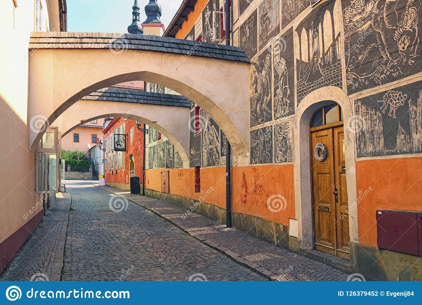 Famous josef vachala street colorful narrow street with archway and black and white pictures in the wall josef vachala litomysl czech republic