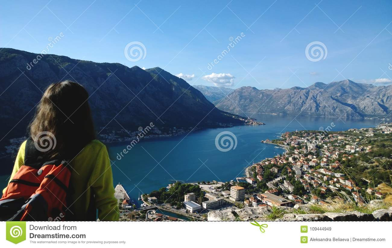 Famous postcard view of the Bay of Kotor in Montenegro. Tourist admires the view, shot from the back