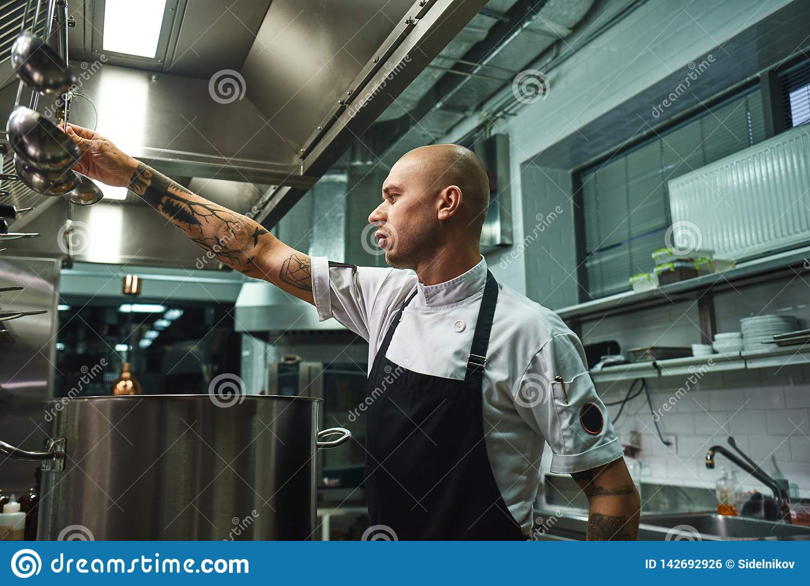 Famous soup. SIde view of attractive bald chef in apron taking a ladle for soup cooking while standing in a restaurant