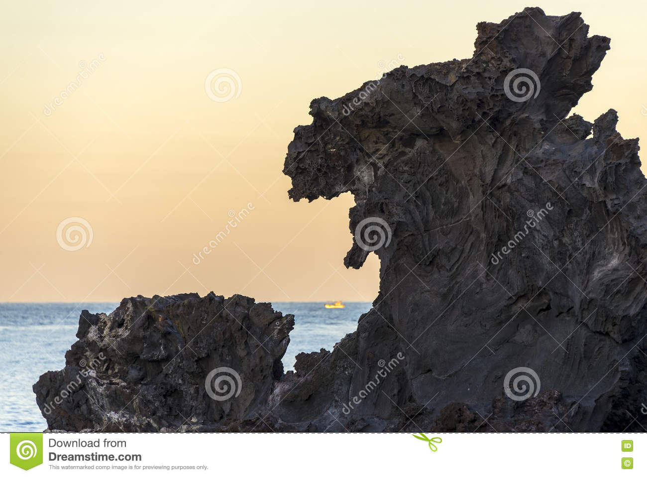 Famous tourist attraction in Jeju island of South Korea. View of Yongduam also known as dragon head rock during sunset.