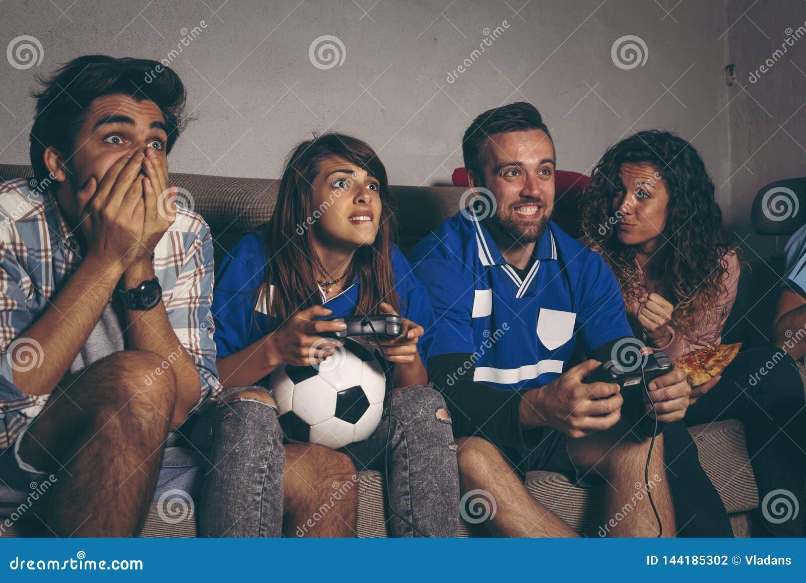 Fanáticos del fútbol que juegan a un videojuego del fútbol