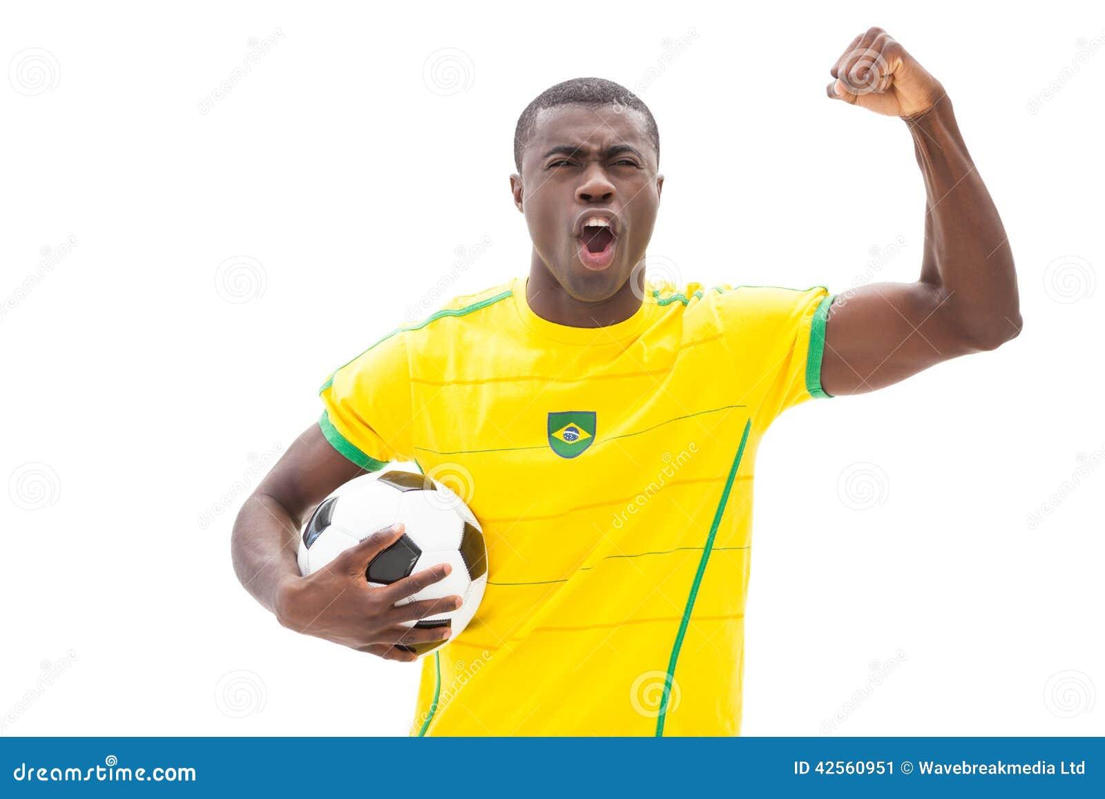 Fan de futebol brasileiro entusiasmado que cheering guardando a bola
