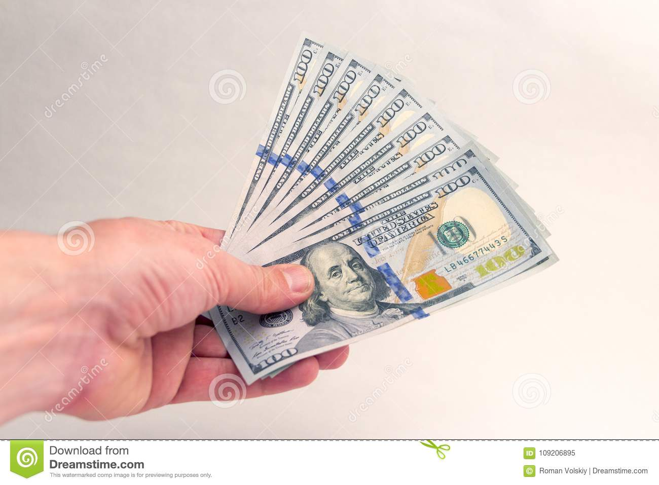 A person gives or takes an American thousand dollars. Fan of Hundred Dollar Bills in the left hand of a man. Bribe or salary. Corr