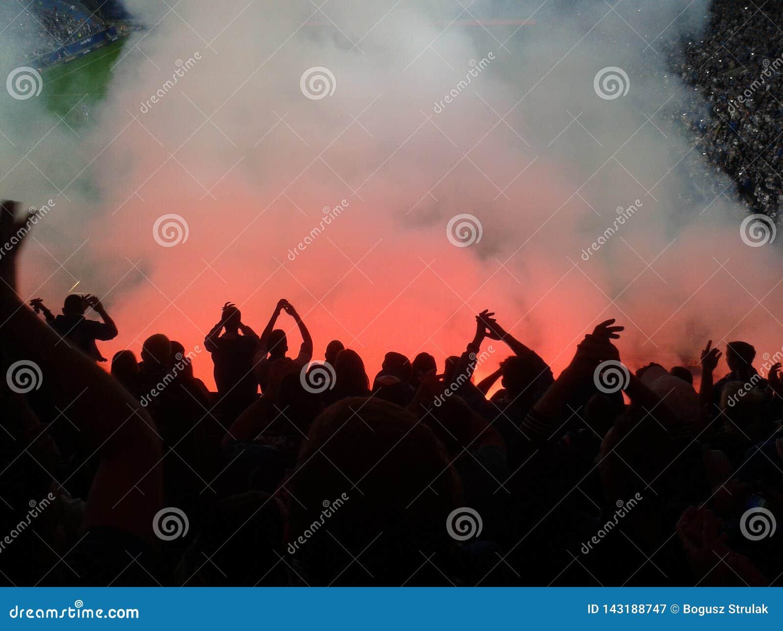 Fan piłki nożnej zaświecający w górę dymów raców i świateł rewolucja protest